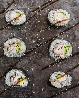 Chiuda sui rotoli di sushi del colpo con i semi di sesamo
