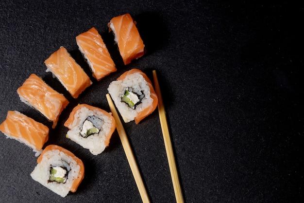 Chiuda sui sushi giapponesi deliziosi dell'alimento sopra fondo scuro