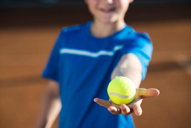 Chiuda sul bambino che tiene una pallina da tennis a disposizione