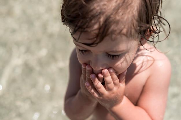 Chiuda sul bambino con gli occhi chiusi giocando in acqua