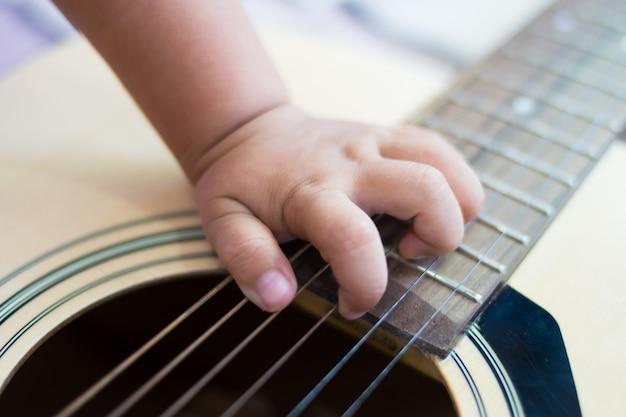Chiuda sul bambino della mano che gioca la chitarra
