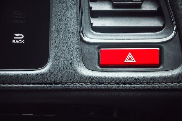 Chiuda sul bottone di emergenza dell'automobile di colore rosso di forma di rettangolo sul cruscotto in automobile di lusso