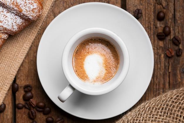 Chiuda sul caffè espresso con i semi del caffè e del croissant