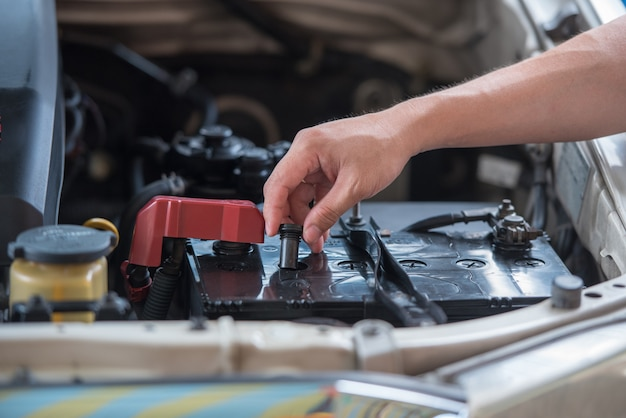 Chiuda sul cappuccio aperto della batteria della mano, concetto della batteria delle automobili di manutenzione.