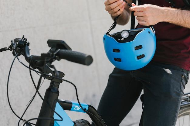 Chiuda sul casco della tenuta dell'uomo sulla bicicletta