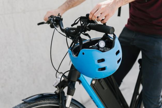 Chiuda sul ciclista che mette il casco sulla maniglia del bycicle
