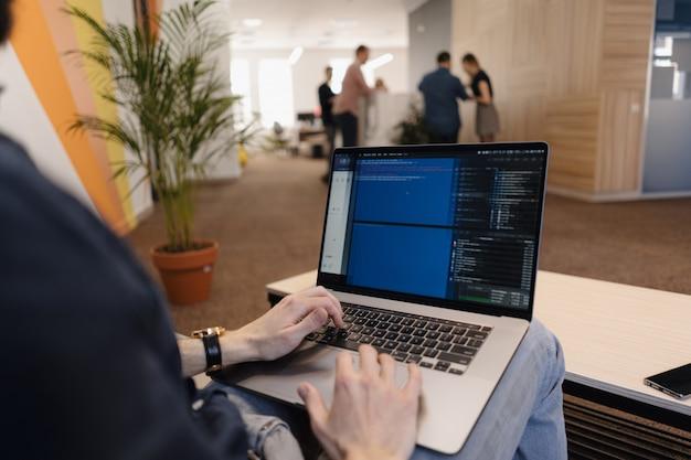 Chiuda sul codice di scrittura dell'uomo sul computer portatile