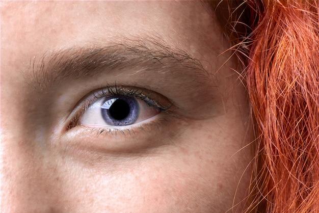Chiuda sul colpo a macroistruzione di un occhio dai capelli rossi della ragazza