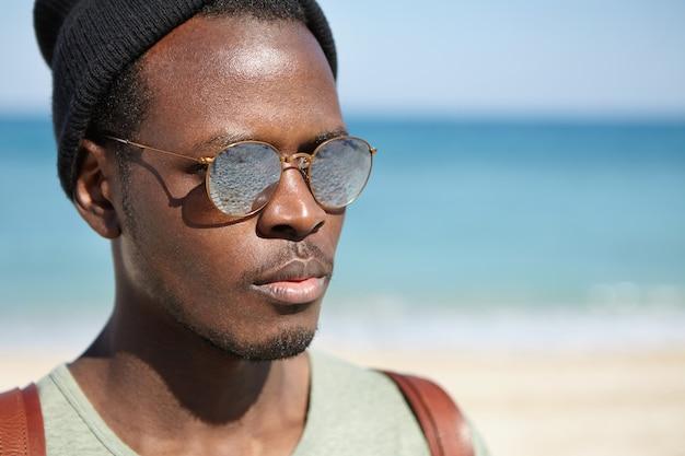 Chiuda sul colpo all'aperto di bei giovani barbuti in posa contro il paesaggio marino offuscato