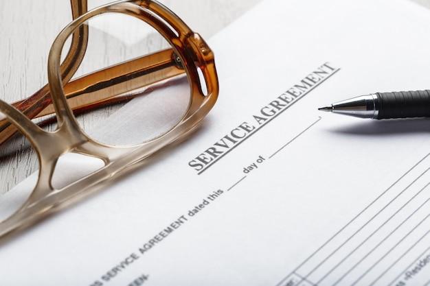 Chiuda sul colpo degli occhiali sul concetto di affari delle carte del documento del contratto