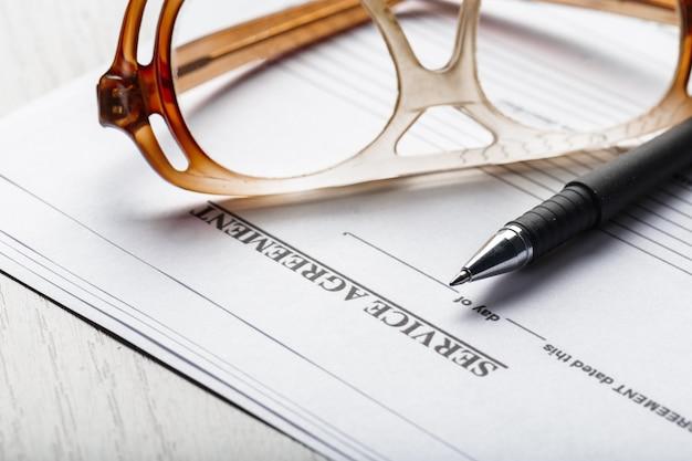 Chiuda sul colpo degli occhiali sul concetto di affari delle carte del documento di contratto