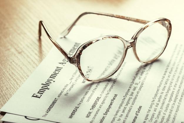 Chiuda sul colpo degli occhiali sulle carte del documento del contratto