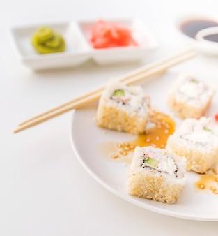 Chiuda sul colpo del piatto dei sushi con fondo vago