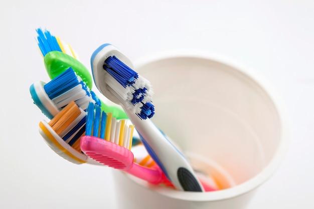 Chiuda sul colpo dell'insieme degli spazzolini da denti multicolori in vetro sulla toilette pulita su fondo bianco, dentale.