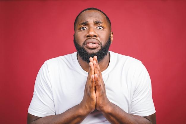 Chiuda sul colpo dell'uomo africano che indossa la maglietta bianca in piedi con sguardo depresso e triste, pensando a qualcosa di brutto è successo, sperando per il meglio. espressioni ed emozioni del volto umano