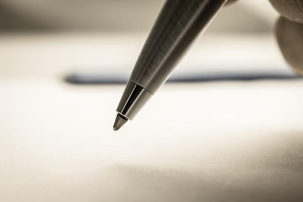 Chiuda sul colpo della mano di un uomo che tiene una penna a sfera sul libro bianco
