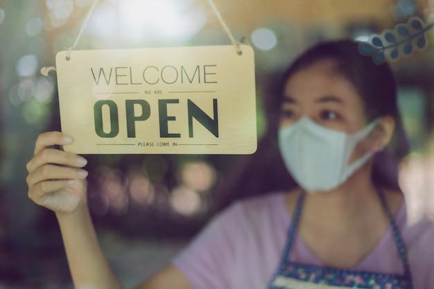 Chiuda sul colpo della scheda d'uso della donna e della mano che girano il bordo aperto del segno sulla porta di vetro in caffetteria.