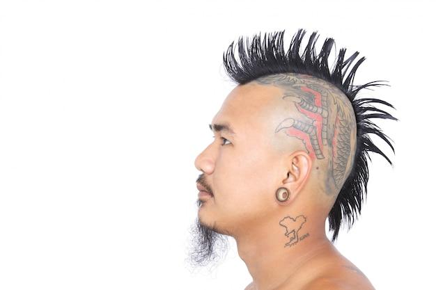 Chiuda sul colpo della testa del punk asiatico con stile di capelli del mohawk, il tatuaggio sulla testa e il piercing dell'orecchio isolati