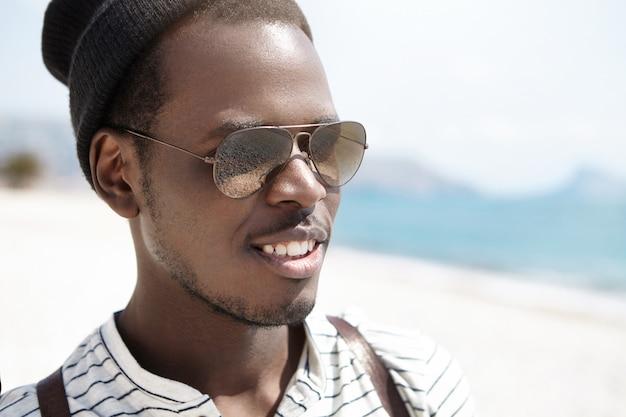 Chiuda sul colpo di giovane viaggiatore con zaino e sacco a pelo afroamericano felice in occhiali da sole a specchio dell'obiettivo che si rilassano sulla spiaggia il giorno soleggiato