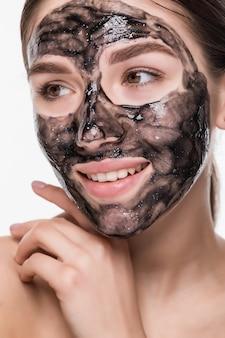 Chiuda sul colpo di una giovane donna di bellezza che usando una maschera di protezione nera isolata