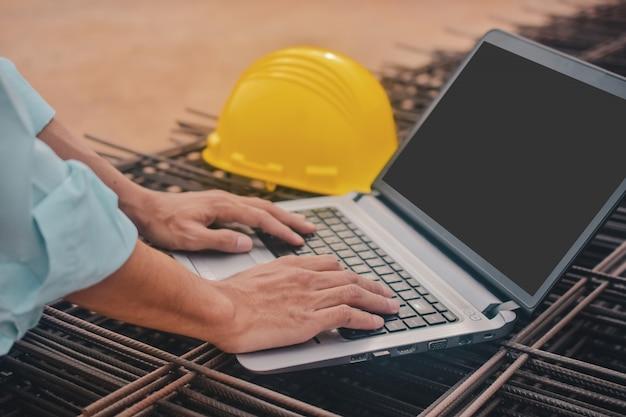 Chiuda sul computer digitante della tastiera di battitura a mano sul cantiere della costruzione del lavoro