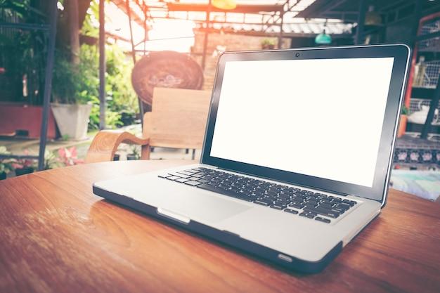 Chiuda sul computer portatile dello schermo in bianco sulla tavola di legno in caffetteria.