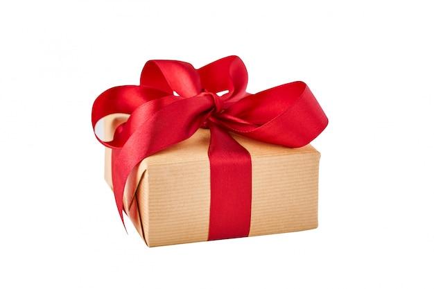 Chiuda sul contenitore di regalo in carta del mestiere con il nastro rosso isolato