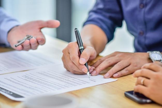 Chiuda sul contratto del segno della mano che compra a casa