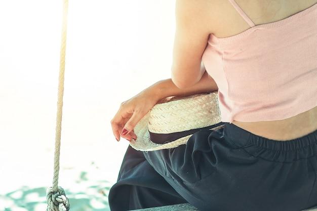 Chiuda sul corpo e sulla mano della donna che abbronza la camicia rosa della pelle sul cappello di paglia che si siede sulla spiaggia.