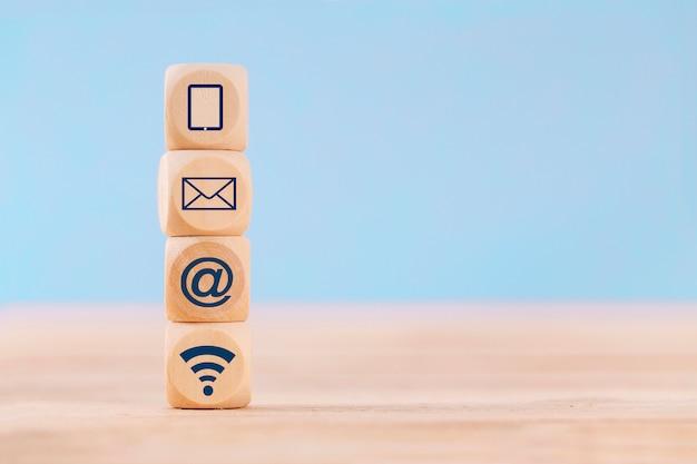 Chiuda sul cubo del blocco di legno con il telefono cellulare, l'e-mail, l'indirizzo e il wifi dell'icona di comunicazione sulla tavola