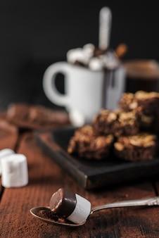 Chiuda sul cucchiaio con la caramella gommosa e molle e lo sciroppo di cioccolato