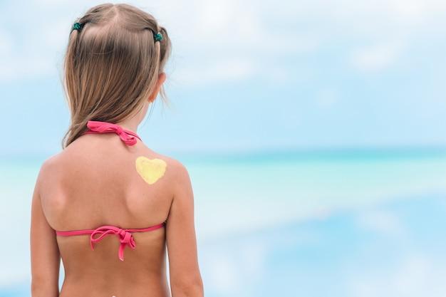 Chiuda sul cuore dipinto dalla crema solare sulla spalla del bambino