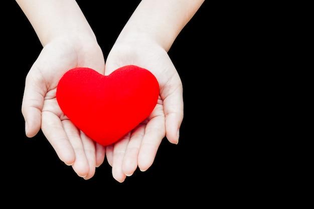 Chiuda sul cuore rosso nelle mani della donna, isolato su sfondo scuro, salute, medicina, persone e concetto di cardiologia