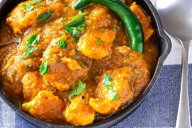 Chiuda sul curry e sul limone del pollo del burro indiano tradizionale serviti con il pane di chapati su ghisa.