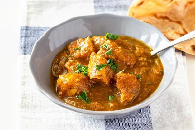 Chiuda sul curry e sul limone del pollo del burro indiano tradizionale serviti con il pane di chapati sul piatto grigio.