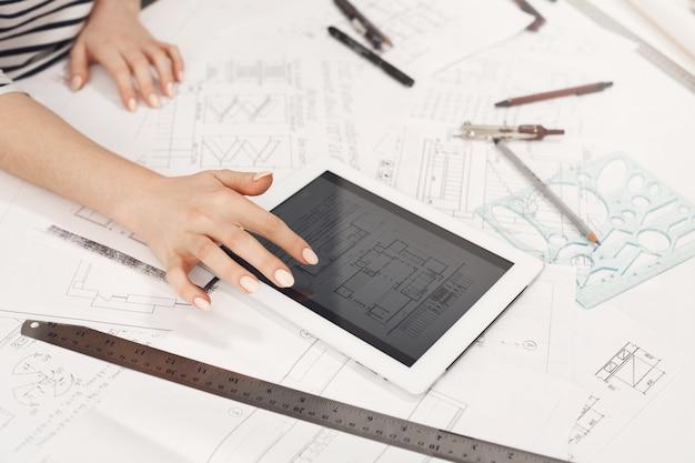 Chiuda sul dettaglio di belle mani femminili dell'architetto che guardano attraverso gli esempi di progettazione degli appartamenti in internet sulla tavola digitale. lavorando su un nuovo progetto