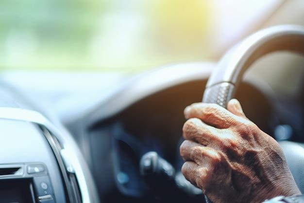 Chiuda sul driver dell'uomo anziano che tiene le mani sul volante