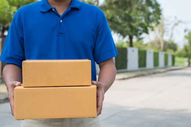 Chiuda sul fattorino in uniformi blu che tengono la scatola di cartone del pacchetto.