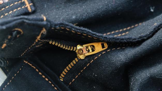 Chiuda sul fondo di struttura dei jeans dei pantaloni della chiusura lampo d'ottone