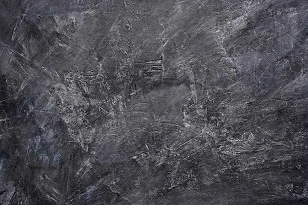 Chiuda sul fondo di struttura della pittura nera di colore sulla parete del cemento.