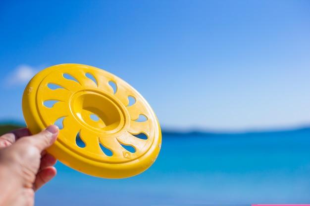 Chiuda sul frisbee, sulla spiaggia tropicale e sul mare