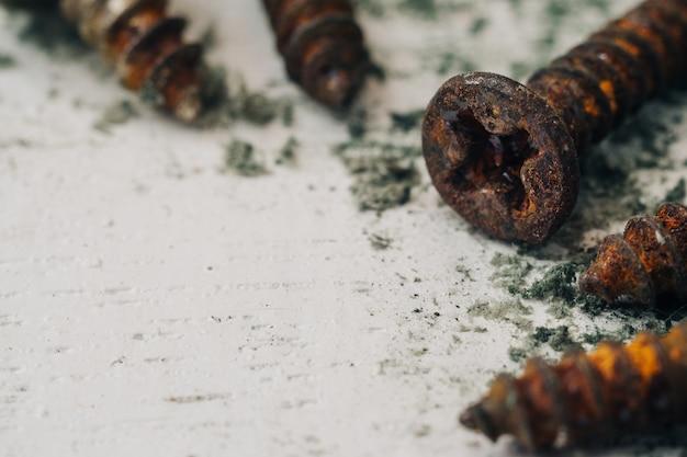 Chiuda sul fuoco selettivo delle viti arrugginite. vecchi bulloni d'acciaio su fondo di legno bianco grungy