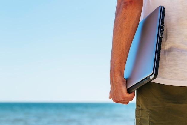 Chiuda sul giovane sulla vacanza che tiene il computer portatile chiuso alla spiaggia