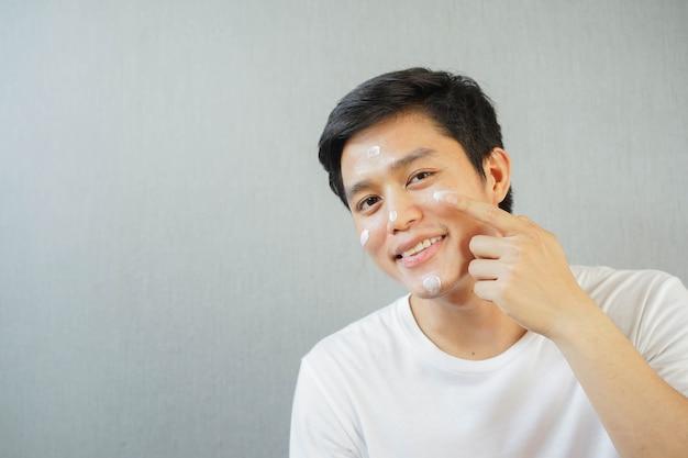 Chiuda sul giovane uomo asiatico che applica la protezione solare uv sul viso