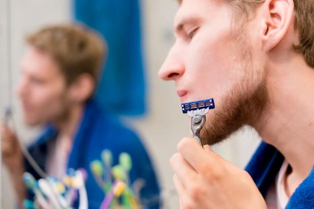 Chiuda sul giovane uomo barbuto che per mezzo del rasoio per radersi la barba di mattina nel bagno