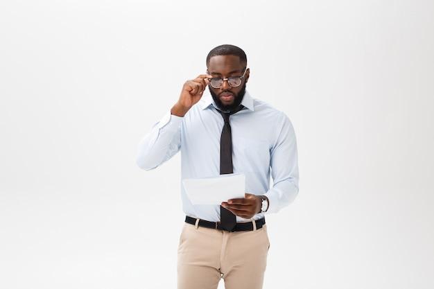 Chiuda sul giovane uomo d'affari afroamericano con l'esame della macchina fotografica mentre tengono la carta del documento