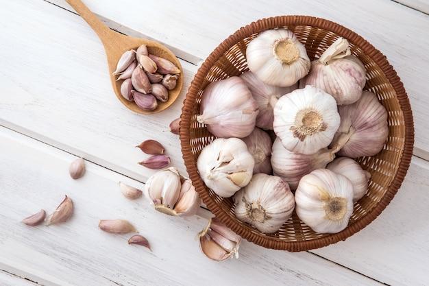 Chiuda sul gruppo di aglio su un piano di appoggio di legno bianco