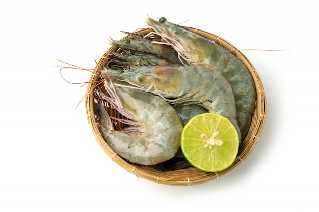 Chiuda sul gruppo di gamberetto bianco pacifico crudo fresco e di limone in ciotola di bambù