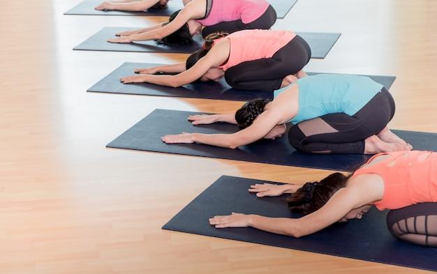 Chiuda sul gruppo di persone che fanno le pose del bambino di yoga nella stanza di addestramento dello studio
