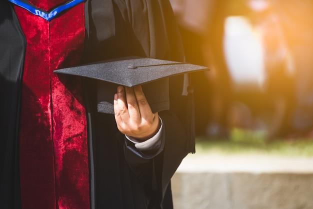 Chiuda sul laureato che tiene un cappello. il concetto ha successo nell'università